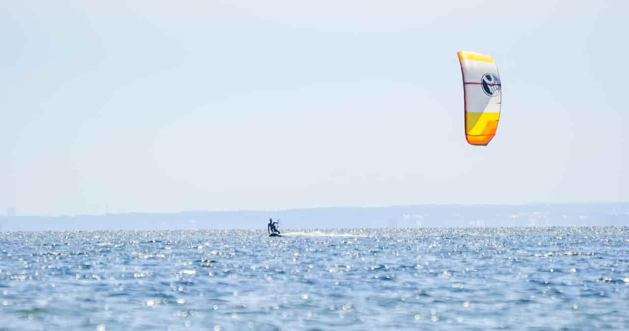 Kitesurfer płynie po pustej zatoce podczas kursu kitesurfingu