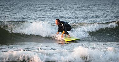 Surfer płynie na małej fali podczas zachodu słońca