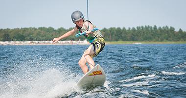 Zawodnik płynie za motorówka uprawiając wakeboarding