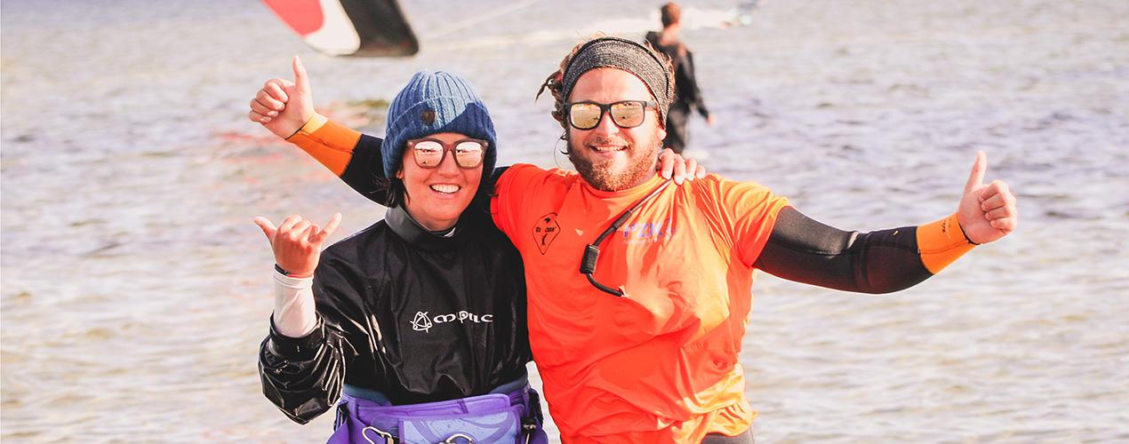 Instruktorka i kursant pozują podczas kursu kitesurfingu