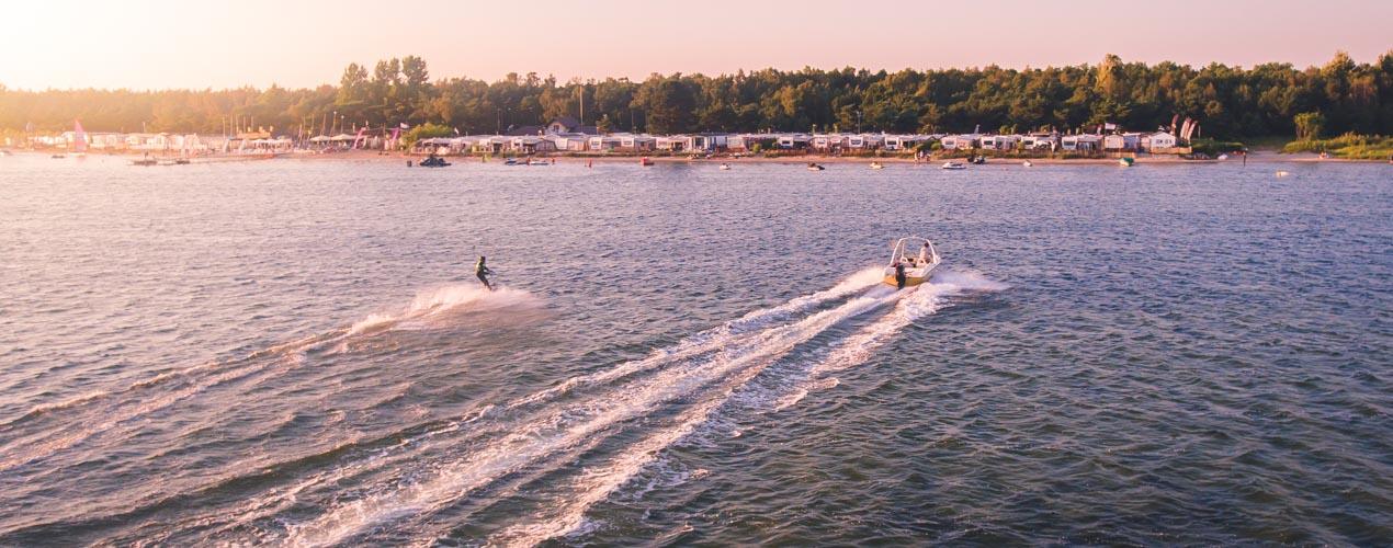 Wakeboarder płynie za motorówką w stronę brzegu