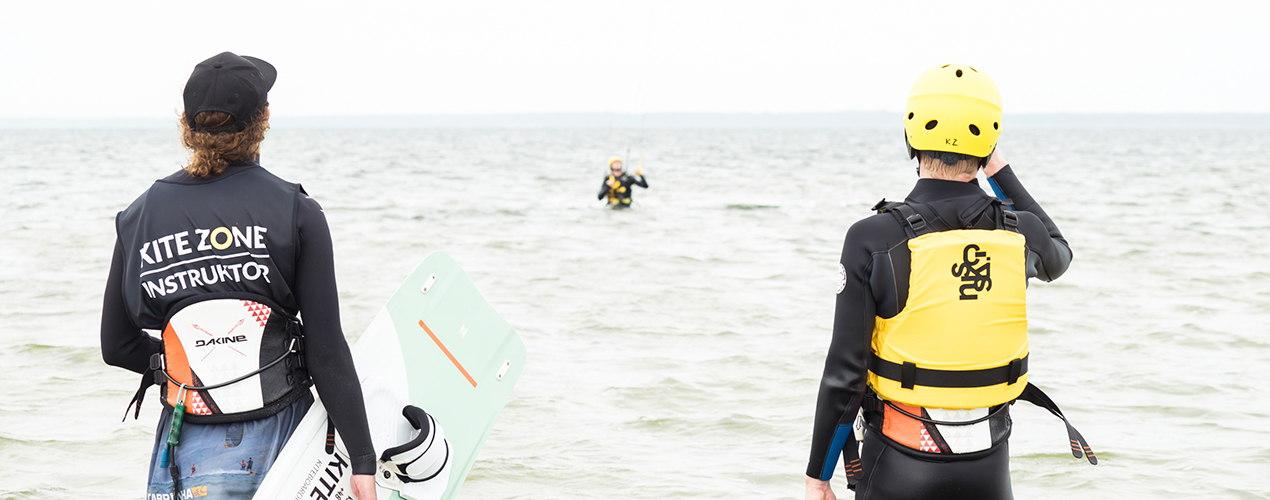 Instruktor kitesurfingu pokazuje podstawy kitesurfingu nad wodą