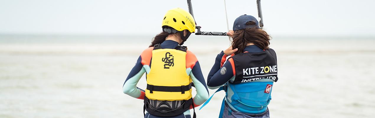Instrukotka kitesurfingu przekazuje latawiec do kitesurfingu kursantce podczas lekcji kitesurfingu