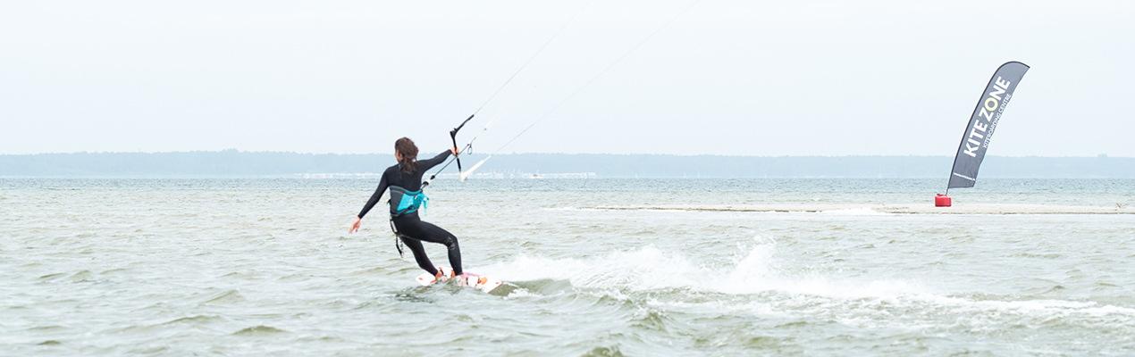 Kitesurferka płynie w lewo na Mewiej Rewie podczas nauki kitesurfingu na Helu